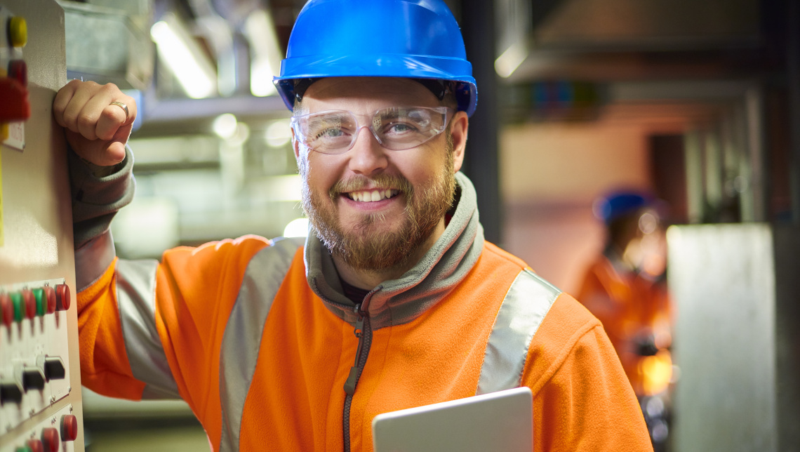 An industrial service engineer smiles to camera before he conducts a safety check of a control panel in a boiler room. He is wearing hi vis, hard hat, safety glasses and holding a digital tablet as he conducts a safety inspection.