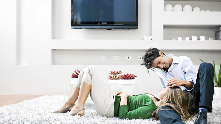 Couple in living room lying on the floor on a carpet