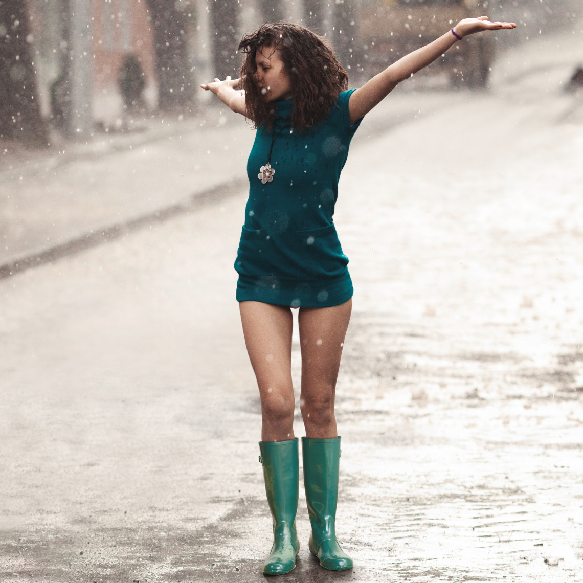 Woman under rain with rubberboots