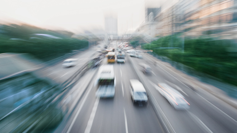 Blurred cars and busses on a street