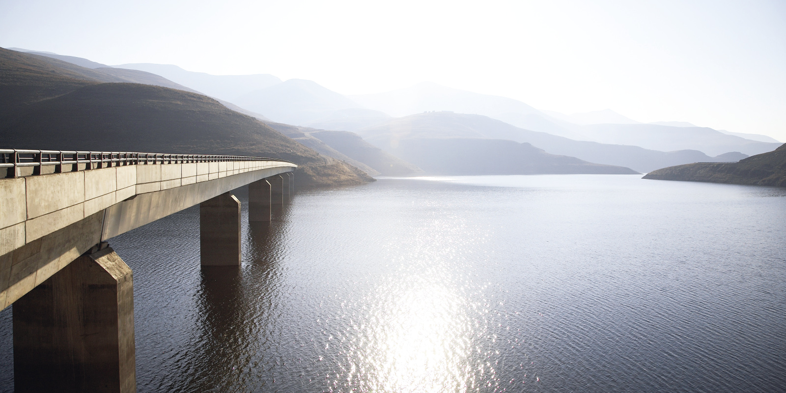 View of bridge going over Katse Dam with sun reflecting off water