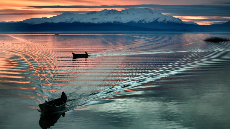 Two fishing boats on a lake in front of a mountain panorama at dusk.